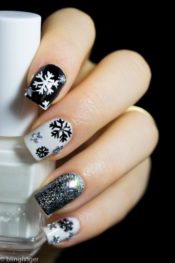 Glittery black and white snowflakes nail design
